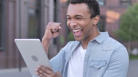 African man celebrating success on tablet outdoor stock video