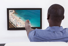 African Man Changing Channel Stock Photo