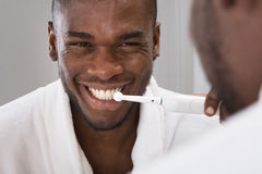 African Man Cleaning His Teeth In Front Of Mirror. Happy African Man Cleaning His Teeth With Toothbrush In Front Of Mirror Royalty Free Stock Photo