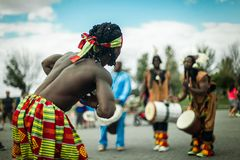 African guy dancing with blurry djembe players in the background stock photo