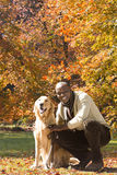 African man and dog in park in autumn Stock Photography