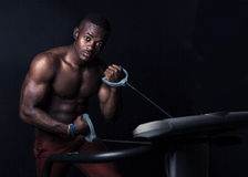 African man doing exercise in dark gym. An African man exercising with gym equipment.  the man has a well developed body Stock Photography