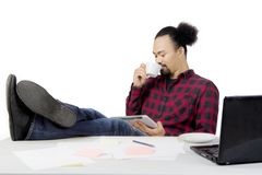 African man drinking coffee on studio. Young African man drinking coffee while sitting with a laptop and his foot on the table, isolated on white background Royalty Free Stock Photography