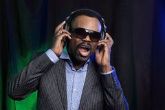 Dance action in a disco club. African man enjoying music in headphones on black Stock Image