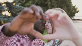 African American man and European girl show heart with hands stock video