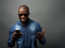 African man excited at mobile phone. Isolated image of african american looking at mobile phone Royalty Free Stock Photos