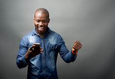 African man excited at mobile phone. Isolated image of african american looking at mobile phone Royalty Free Stock Photography