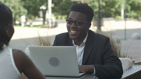 African man explaining business strategy to his african female colleague, using laptop during meeting at a cafe