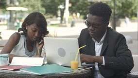 African man and female colleague working together, using gadgets during meeting at a cafe Stock Photography