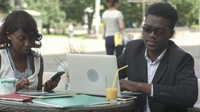 African man and female colleague working together, using gadgets during meeting at a cafe