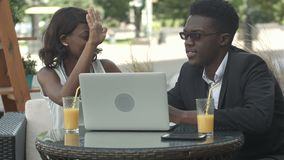 African man in formal suit explaining business strategy to his African female colleague using laptop during meeting. Giving high five at a cafe. Professional stock video footage