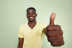 African man gesturing thumbs up sign by green wall Stock Photos