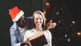 African man giving surprise christmas gift for woman. African man giving surprise christmas gift for woman stock footage