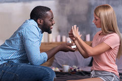 African man giving wedding present to his girlfriend. Be mine. African young happy men giving wedding present to his girlfriend and making proposal while she Stock Image