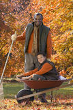 African man and grandson doing yard work in autumn Stock Photo