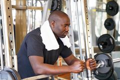 African man in the gym. African man is concentrated on a power exercise with a barbell in the gym. A man resting after exercise with weight. The concept of Stock Photography