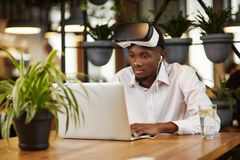 African man in head set of virtual reality using laptop. Stock Photo
