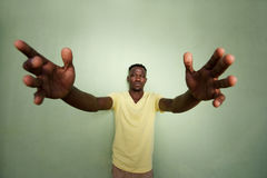 African man with his arms outstretched standing against green wall Royalty Free Stock Photography