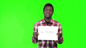 African man hold i am hungry sign. African man in a plaid shirt holds up a i am hungry sign at the camera over a green background with copy space stock footage