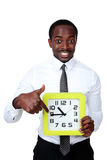 African man holding a clock Stock Photo