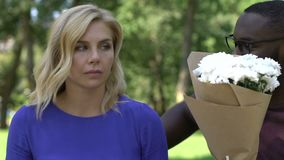 African man holding flowers, being late on date with blond caucasian girlfriend. Stock footage stock video footage