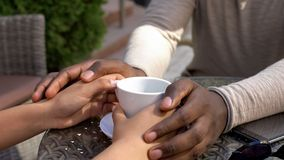 African man holding girlfriend hands, romantic date in cafe, love expression royalty free stock photography