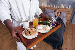 African man holding the tray with breakfast in bedroom Stock Images