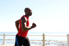 African man jogging on seaside promenade Royalty Free Stock Photography