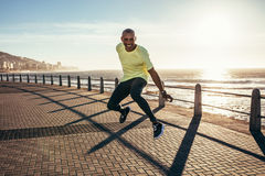 African man jumping on a road by the sea. Young african man jumping on a road by the sea. Excited young runner jumping Royalty Free Stock Image