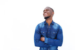 African man laughing with arms crossed against white background Royalty Free Stock Image