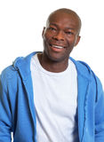 African man laughing after workout. Friendly man from South Africa in a blue jersey on a white background Stock Image