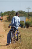 African Man leaning on bicycle Royalty Free Stock Image