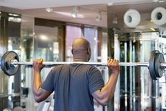 African man lifting a barbell. Back view royalty free stock photos