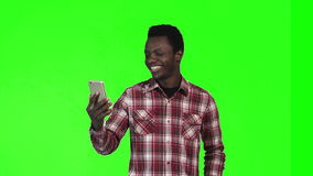 African man make video call. African young man make video call using smartphone on green screen background stock video footage