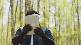 An african man with medical mask using the tablet in the forest. wireless or future technology concept