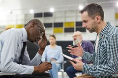 African Man in Mental Health Consultation. Side view portrait of mature psychologist consulting African men in therapy session, copy space stock image
