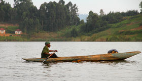 African Man Paddles Dugout Canoe. LAKE BUNYONI, UGANDA - CIRCA SEPTEMBER 2012- An African man paddles his dugout canoe through the waters of Lake Bunyoni in stock photo