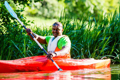 African Man paddling with canoe on forest river Royalty Free Stock Photo