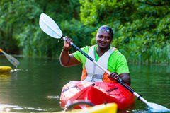 African Man paddling with canoe on river Royalty Free Stock Photography