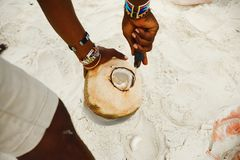 African man peels coconut on the beach. On sunny day Royalty Free Stock Image