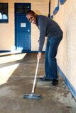 African man performing community service volunteer cleaning work at township school