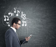 African man with a phone, music notes blackboard Stock Image