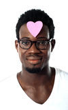 African man with pink paper heart on forehead Stock Image