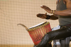 African man planing drum. African man, leather pants, playing drum, bracelets Stock Image