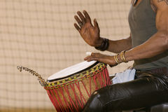 African man planing drum. African man playing drum with hands, one hand raised, palm view Stock Photo