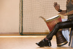 African man playing drum. African man, leather pants, playing drum, bracelets Stock Photo