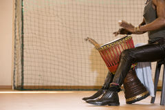 African man playing drum. African man, leather pants, playing drum, bracelets Stock Images