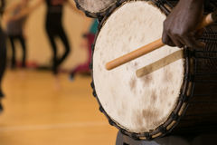 African man playing drum. African man playing traditional drum, close up view from left side behind Royalty Free Stock Images