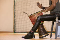 African man playing traditional instruments. African man, leather pants, playing drum, bracelets Royalty Free Stock Photos