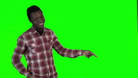 African man pointing on green. Modern african smiling man pointing with both hands towards blank copy space on a bright green background, upper body side view stock footage